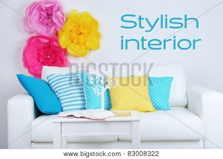 White sofa with colorful pillows in room on wall background, Stylish Interior concept