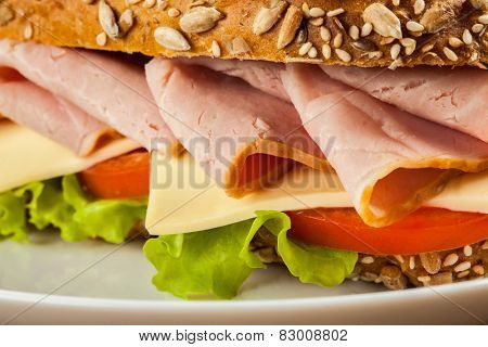 Ham sandwich with lettuce, cheese, tomato close up