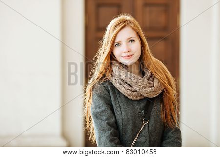 Young beautiful redhead woman wearing coat and scarf posing outdoors