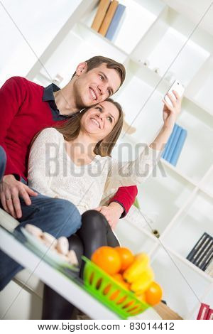 Smiling couple taking self portrait picture with telephone at home, selective focus