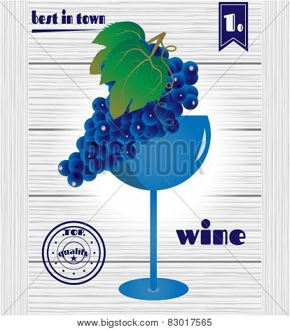 Glass with blue, wine grape on wooden background with text