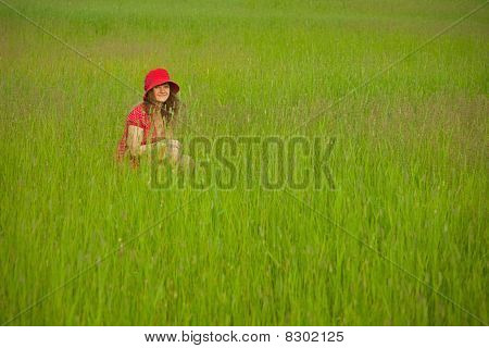 Woman In Red Clothes Sits In Green Grass