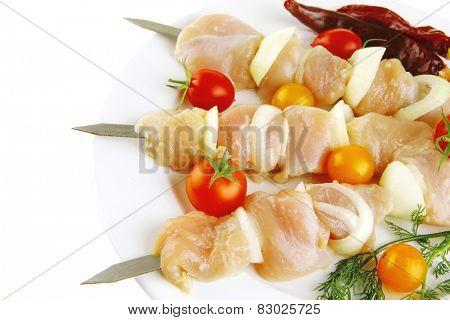raw chicken shish kebab on white plate