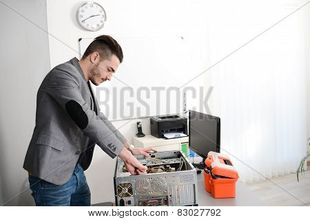 handsome young man computer repair fixing a pc at customers house