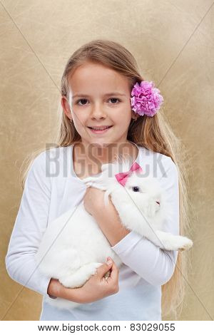 Cute little girl holding her white rabbit - portrait on golden background- shallow depth of field