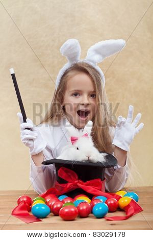 Little magician girl conjuring the easter bunny and colorful eggs- shallow depth of field