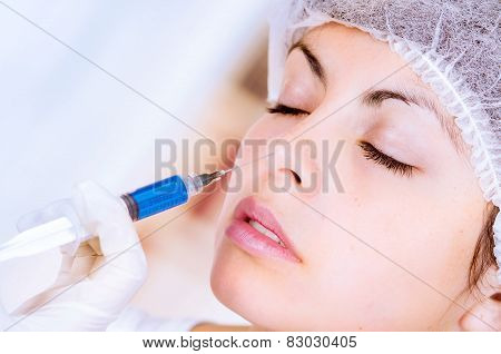 closeup of woman receiving cosmetic injection through nose