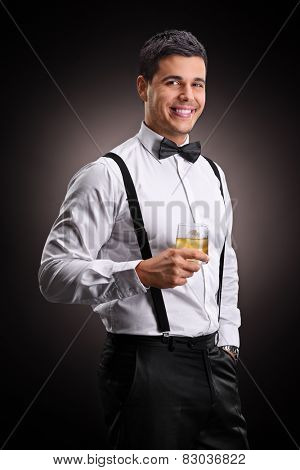 Vertical shot of a cheerful man drinking bourbon on black background