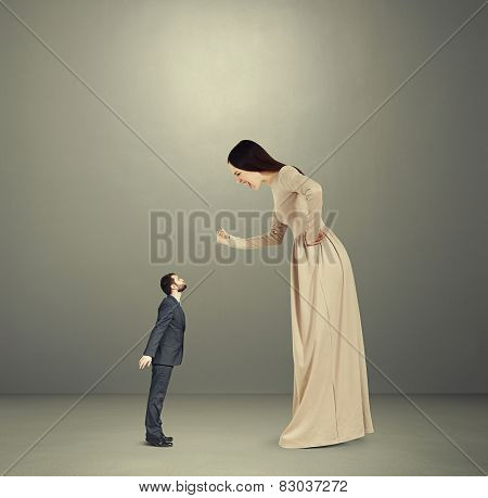 dissatisfied young woman screaming and showing fist to small kissing man. concept photo in empty grey room