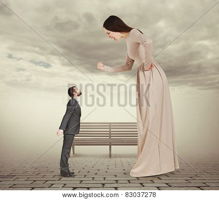 angry screaming woman showing fist and looking down at small kissing man. concept photo in foggy park