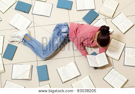 Young woman lying on floor with books and reading, top view. Blurred text is unreadable