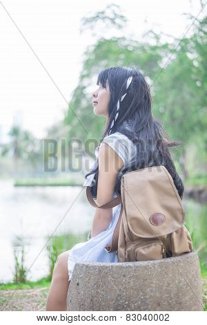 A Cute Asian Thai Girl Is Relaxing On A Rock Seat Letting Her Thoughts Fly. This Photo Use Soft Japa
