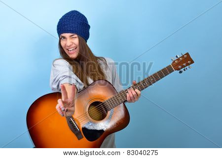 young woman playing music on acoustic guitar