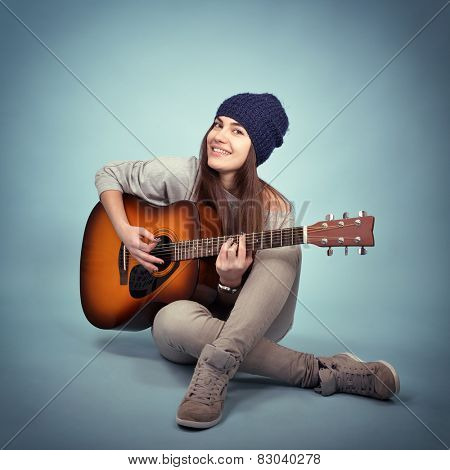 young woman playing music on acoustic guitar, toned