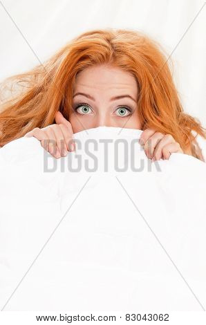 Amazed woman is lying in bed under blanket and looking at camera