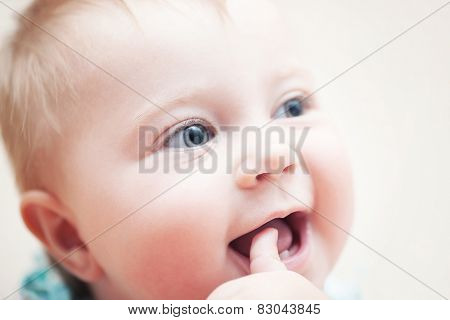 Closeup portrait of happy funny baby with finger in the mouth, adorable sweet child with beautiful grey eyes, healthy childhood