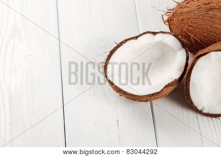 Cracked coconut on wooden table.