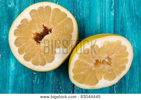 Pomelo fruit on wooden surface.