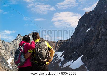 Young Tourist Couple Standing  On Stone Near Mountain Lake