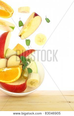 Fresh fruit salad with pieces flying out of a bowl isolated