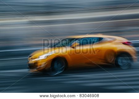 Yellow Sports Car In A Blurred City Scene