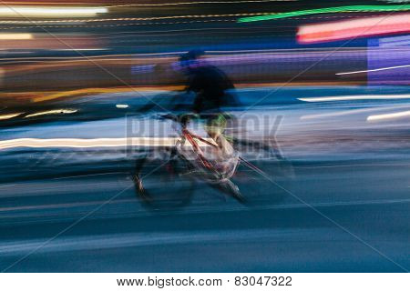 Man Riding A Bicycle In A Blurred City Scene