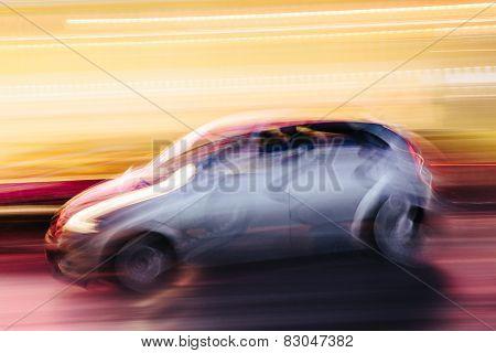 Grey Compact Car In A Blurred City Scene