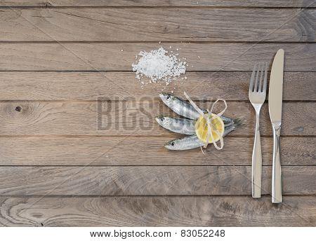 Three sardines, salt and fork with knife