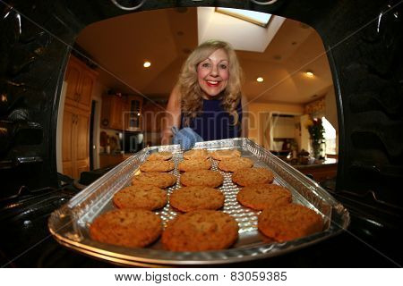 Hot and Fresh COOKIES right from the oven!  A lady bakes cookies for a charity bake sale to help raise money for a noble cause.