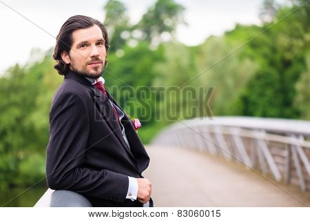 Wedding bridegroom outside at bridge