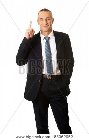 Businessman pointing upwards with one hand.