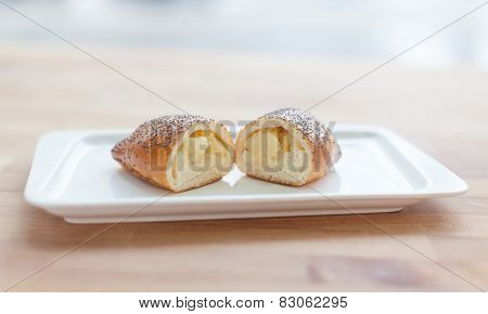 Beautiful delicious cake with cream filling on a plate. Cut in half.