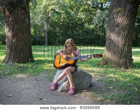Young Girl Playing Acoustic Guitar Outdoors In Summer