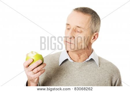 Mature man eating healthy apple.