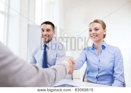 business, people and teamwork concept - smiling businesswoman making handshake gesture with group of businesspeople in office