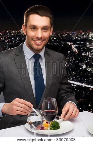 restaurant, people and holiday concept - smiling man eating main course at restaurant