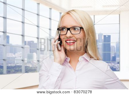 business, style and people concept - smiling businesswoman, student or secretary in eyeglasses calling on smartphone over office window with city view background