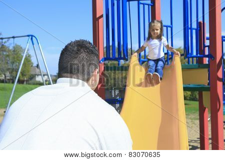 A Father and daughter playing on a slide
