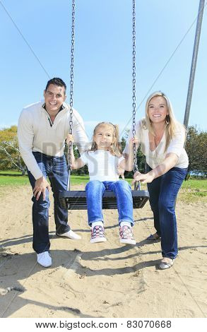 Girl sitting on a swing, father on mother pushing