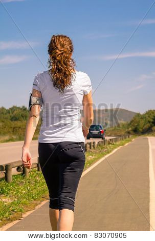 Young woman with arm support band for smartphone walking