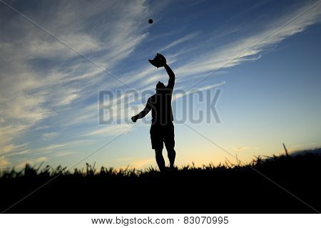 A man silhouetted by the sunset is just beginning catch ball with glove