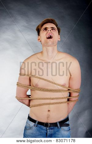 Tortured shirtless man tied with a rope.