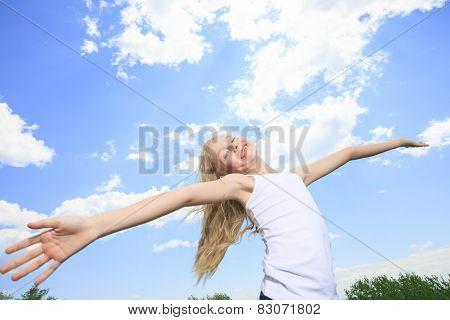 A smiling little girl in white blank t-shirt over blue sky backg