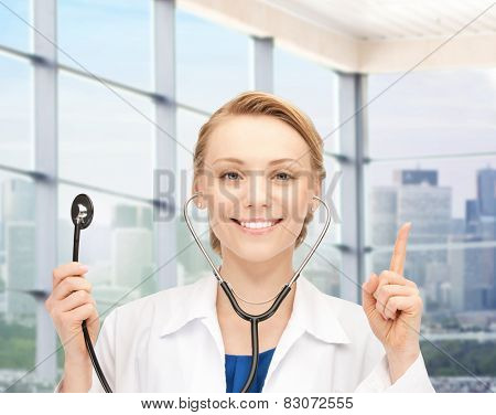 people, medicine and gesture concept - happy female doctor with stethoscope pointing her finger up over clinic background