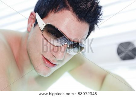 A man in a sunbath receiving high degree of ultraviolet light.
