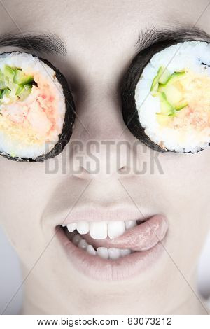 Funny picture of woman with sushi roll on her eye. Isolated on w
