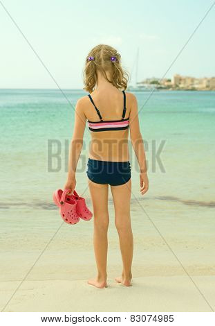 Little Girl With Flip Flops Standing On The Beach.