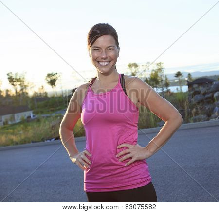 A woman jogging in a urban place with house in the background