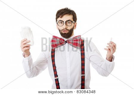 Surprised man wearing suspenders with menstruation pad.