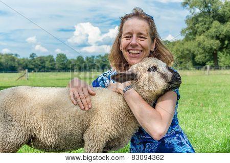 Woman embracing and hugging young sheep